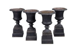 A set of four black painted cast iron garden urns