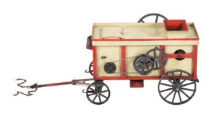 A cream and red painted tinplate model of a threshing machine