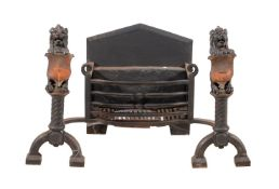 A Victorian wrought and cast iron and copper mounted fire grate