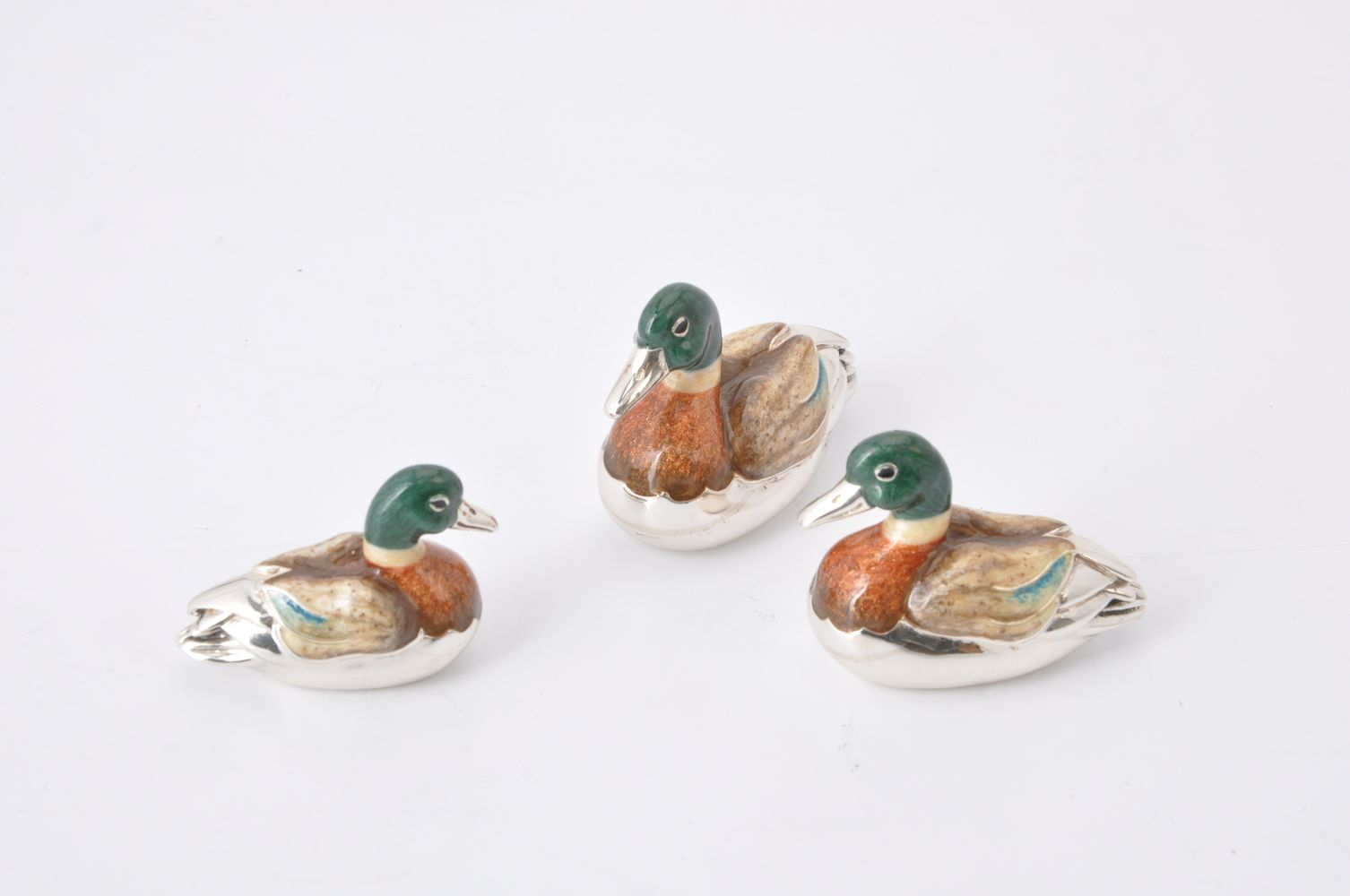 Lot 668 - A graduated set of three silver and enamel model ducks by J A H