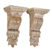 A pair of limed carved oak wall brackets