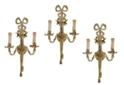 A set of three Continental gilt metal twin light wall appliques in Louis XVI taste