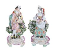 A pair of Derby porcelain bocage figures of a musician and companion