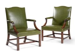 A pair of mahogany and brass studded green leather upholstered armchairs, in George III style, 19th