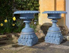 A pair of Victorian blue painted cast iron garden urns on plinths