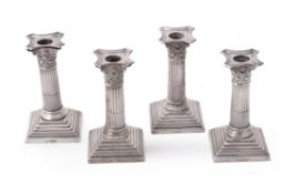 Four late Victorian silver Corinthian candlesticks by William Hutton & Sons Ltd.