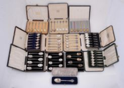 A collection of twelve cased sets of silver and silver coloured spoons