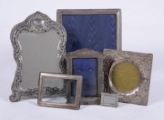A collection of silver mounted photo frames and a silver mounted mirror