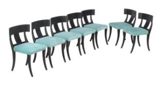 A set of fourteen ebonised dining chairs