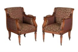 A pair of mahogany and upholstered armchairs in Regency style