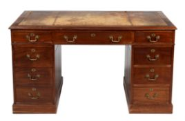 An Edwardian mahogany and leather inset pedestal desk