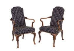 A pair of walnut and upholstered armchairs