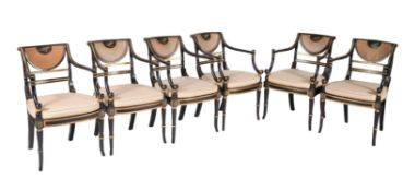 A set of twelve ebonised and parcel gilt armchairs