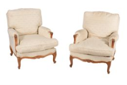 A pair of French carved beech and upholstered armchairs