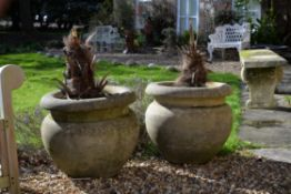 A pair of stone composition garden urns