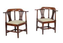 A pair of George III mahogany corner armchairs