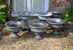 A matched set of six Victorian painted cast iron urns