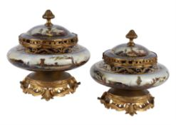 A pair of French porcelain and gilt metal mounted potpourri urns and covers