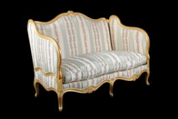 A French carved giltwood sofa in Louis XV style