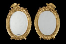 A pair of French carved giltwood oval mirrors
