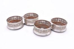 A set of four George IV silver circular coasters by Sebastian Crespel II