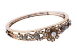 An Edwardian half pearl and cat's eye chrysoberyl hinged bangle