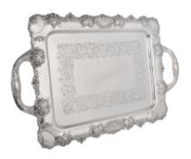 A late Victorian silver shaped rectangular twin handled tray by John Hines