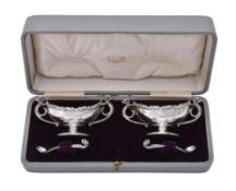 A cased pair of matched Edwardian oval pedestal salt cellars