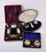A cased pair of Edwardian silver shell shaped salts and spoons by Mitchell Bosley & Co.