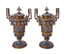 A pair of French gilt metal and champlevé enamel twin handled side or garniture urns and covers