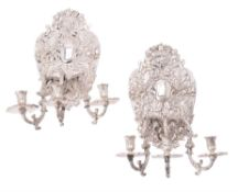 A pair of silvered metal three light sconces in William and Mary taste