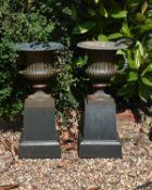 A pair green painted cast iron garden urns