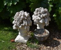 A pair of reconstituted stone finials modelled as fruit and flower vases