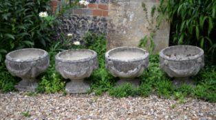 A set of four stone composition garden urns