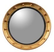 A giltwood and composition convex wall mirror in Regency style
