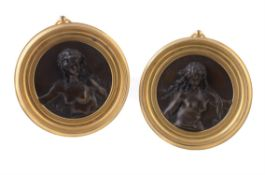 A pair of French patinated bronze relief roundels of nymphs
