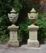 A pair of English limestone and composition urns on plinths