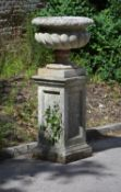 A stone composition garden urn on plinth