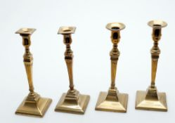 Two pairs of George III brass candlesticks