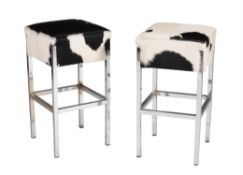 A pair of cow hide upholstered chrome bar stools