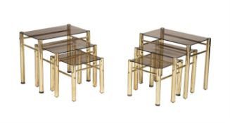 A pair of metal and glass nests of three occasional tables