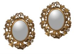 A pair of small carved giltwood oval wall mirrors