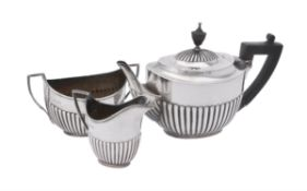 A Victorian silver three piece oval half gadrooned tea set by William Hutton & Sons