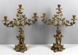 A pair of late 19th century French gilt bronze and brass figural three light candlesticks
