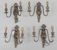 A set of four gilt metal twin light wall appliques