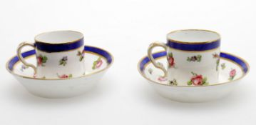 A pair of later decorated Sevres coffee cups and saucers