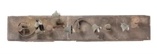 A metal and pine board of servant's bells