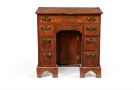 A George I walnut and feather banded kneehole desk