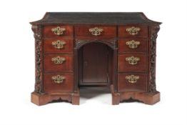 A George II mahogany serpentine kneehole desk