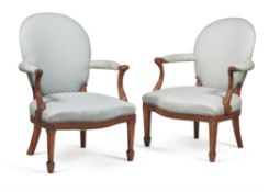 A matched pair of George III mahogany and upholstered open armchairs